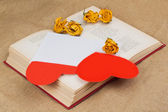 Two hearts in the envelope with dried roses lying on the book — Stock Photo