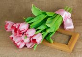A bouquet of pink tulips with satin ribbon luing on the frame — Стоковое фото