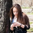 Young girl with smart phone leaning on the old big tree — Stock Photo #69493251