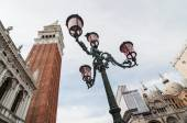 Beautiful ornate lampposts in Piazza San Marco against campanile — Stock Photo