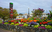 Garden and totem on the banks of Victoria Inner Harbour, British Columbia, Canada — Stock Photo