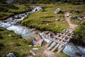 Wooden bridge across running river in the countryside — Stock Photo