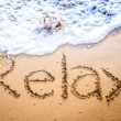 Relax written into the sand on a beach — Stock Photo #63859025