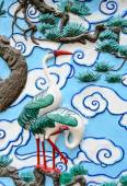 Bas relief sculpture of crane on the tree with cloud background — Stock Photo