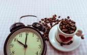 Alarm clock and lovely coffee cup filled with coffee beans for t — Foto de Stock