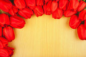 Red tulips on a wooden background — Stock Photo