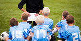 Football soccer match for children. Boys and coach sitting on green grass. — Stock Photo