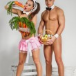 Couple in rabbit costumes with carrots and eggs — Stock Photo #65674077