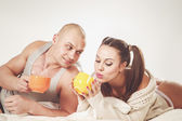 Couple lying on bed with cups of tea — Stock Photo