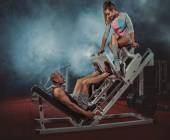 Man doing legs presses with trainer — Stock Photo