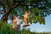 Girl on  swing with parents — Stock Photo
