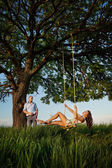 Beautiful girl on  swing  with boyfriend — Stock Photo