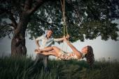 Girl with boyfriend on  swing — Stock Photo