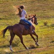 Woman in blue jeans riding a horse — Stock Photo #74215517