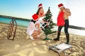 Santa's helpers and Santa at  tropical beach — Stock Photo