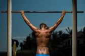Athlete doing pull-up on horizontal bar — Stock Photo