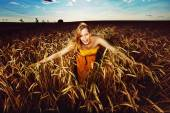 Pretty girl is making merry on the wheat field  on the sunset ba — Stock Photo