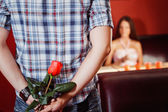 Man is hiding a red rose to make a gift to his girl at their dat — Stock fotografie