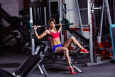A young healthy athletic woman is pushing weight at gym. — 图库照片