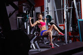 A young healthy athletic woman is pushing weight at gym. — Stock Photo