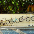 A row of retro bicycles are hanging on a street wall in unusual — Stock Photo #70179137