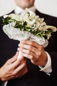 Closeup vertical image of a groom holding wedding spring flowers — Stock Photo