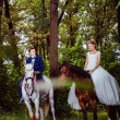 A couple of beautiful young newlywed are sitting on the horses a — Stock Photo #71354313