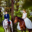 A couple of beautiful young newlywed are sitting on the horses a — Stock Photo #71354319