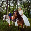 A couple of beautiful young newlywed are sitting on the horses a — Stock Photo #71354343