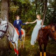 A couple of beautiful young newlywed are sitting on  horses and — Stock Photo #71396873
