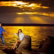 Beautiful young woman is holding her boyfriend by hand at a stunning golden seascape sunset background. — Stock Photo #74360575