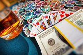 A poker table with chips, glass of wiskey, bundle of money and heart flash royal combination of playing cards. — Stock Photo