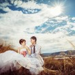 Beautiful wedding couple is sitting high on a hill at blue cloudy sky background and tenderly touching by hands. — Stock Photo #74415915