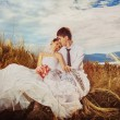 Beautiful wedding couple is sitting high on a hill at blue cloudy sky background and tenderly embracing. — Stock Photo #74592561