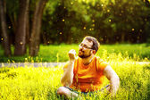 Friendly happy man is sitting with closed eyes in fresh green park grass at sunny summer trees background. — Stock Photo