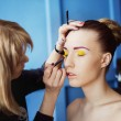 Professional makeup process. Artist is making face style of a young beautiful model at  blue studio background. — Stock Photo #74987757
