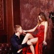Elegant young man is kissing his beautidul young girl in red dress in bedroom. — Stok fotoğraf #76042925