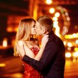 Beautiful young woman in red sparkling dress is passionately kissing elegant macho man at city street at bright lights blurred background. — Stock Photo #76043069