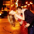 Handsome young man is kissing beautiful elegant woman in red dress at yellow street lights background. — Stock Photo #76043077