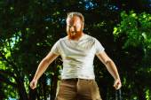 Macho man with red beard is smiling and putting hands down showing atrraction at green summer outdoor background. — Stock Photo