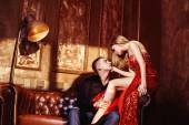Beautiful glamour young couple is kissing in bedroom sitting on sofa. — Stock Photo