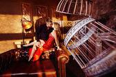 Beautiful happy couple is flirting sitting on sofa at interior background with golden sunset sunlight. — Stockfoto