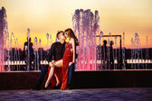 Beautiful young woman in red dress and macho man are kissing at colored water fountain at orange sunset sky background. — Stock Photo