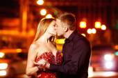 Beautiful young woman in red sparkling dress is passionately kissing elegant macho man at city street at bright lights blurred background. — Stock Photo