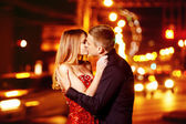 Beautiful young woman in red sparkling dress is passionately kissing elegant macho man at city street at bright lights blurred background. — ストック写真