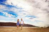 Beautiful young couple is walking along  river coast with yellow sand at blue summer cloudy sky background. — Stock Photo