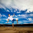 Young strong man is training taekwondo outdoors at beach at blue summer sky background. — Stockfoto #78123022