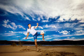 Young strong man is training taekwondo outdoors at beach at blue summer sky background. — Стоковое фото
