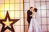 Happy beautiful wedding couple is kissing at bright window with yellow light and star background. — Stock Photo