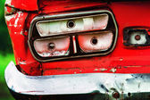 Closeup image of vintage rusty red car headlight at green background. — Stock Photo